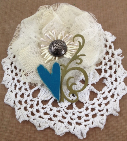 Crocheted doily, chipboard, fabric flower, metal button & paper swirl